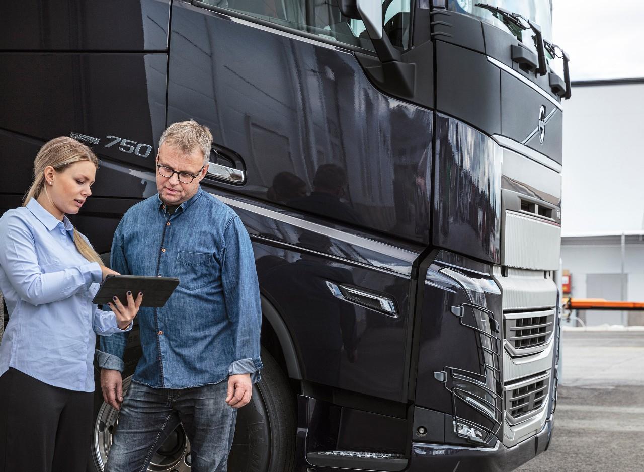 Vīrietis un sieviete stāv kravas automašīnas priekšā un skatās uz planšetdatoru