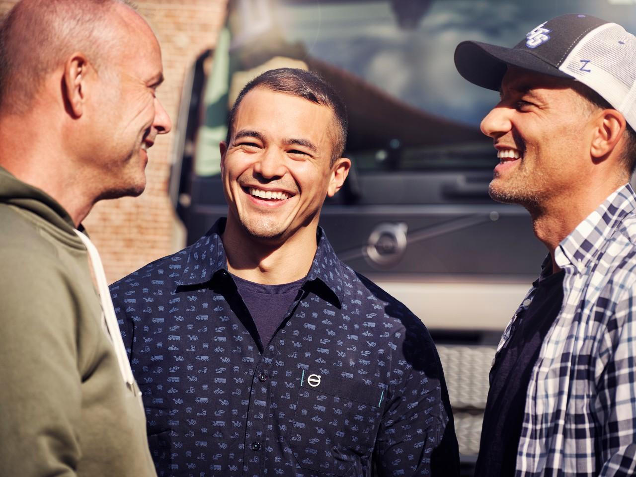 Trīs vīriešu tuvplāns, kas smaida pie Volvo kravas automašīnas